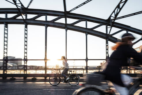 Young cyclist on a bridge at sunset - WFF00138