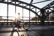 Young cyclist on a bridge at sunset - WFF00141