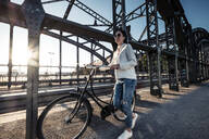 Young cyclist on a bridge at sunset - WFF00144
