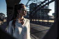 Young woman on a bridge in the evening light, seen through bridge pier - WFF00147