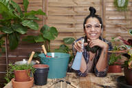 Portrait of a smiling young woman gardening on her terrace - IGGF01387