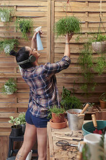 Happy woman spraying water on plants on her terrace while listening to music - IGGF01393