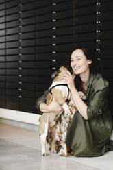 Portrait of happy woman cuddling her dog - EYAF00631