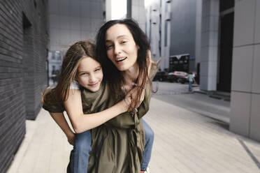 Portrait of mother giving her daughter a piggyback ride - EYAF00634