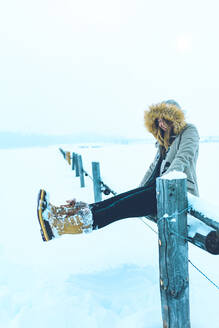 Cheerful woman sitting on railing at snow covered field during winter - CAVF68241