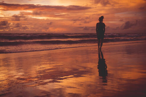 Rear view of woman standing at beach against dramatic sky during sunset - CAVF68256