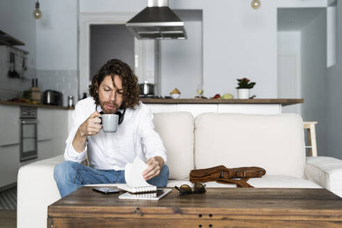 Man sitting on couch at home with coffee mug and notepad - GIOF07478