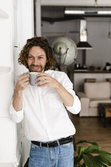 Smiling man having a coffee break at home - GIOF07493