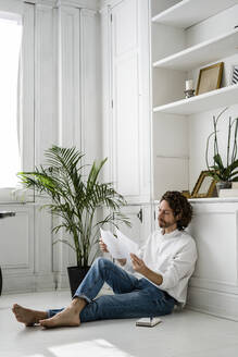 Man sitting on the floor at home reviewing papers - GIOF07499