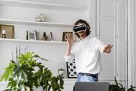 Man at home using VR glasses - GIOF07508