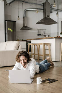 Smiling man lying on the floor at home using laptop - GIOF07514