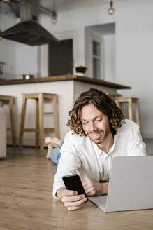 Smiling man lying on the floor at home using cell phone and laptop - GIOF07517