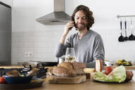 Man on the phone in kitchen at home - GIOF07532