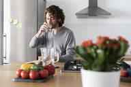 Man drinking water and reading book in kitchen at home - GIOF07535