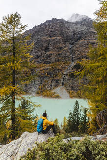 Hiker sitting and looking on lake at alpine plateau in autumn, Sondrio, Italy - MCVF00063
