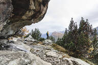 Hiker standing and looking over alpine plateau in autumn, Sondrio, Italy - MCVF00066