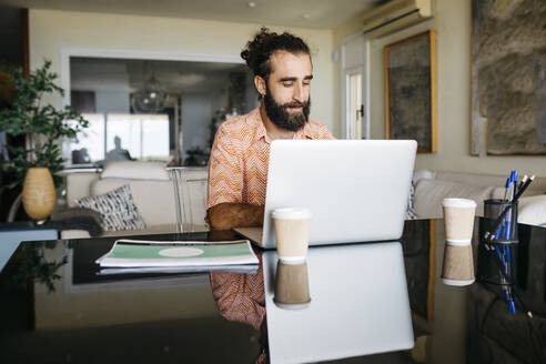 Man working on table at home using laptop - JRFF03868