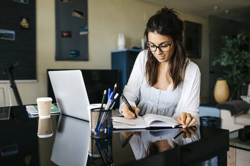 Woman working on table at home taking notes - JRFF03871
