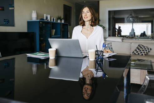 Woman working on table at home with notebook and laptop - JRFF03874