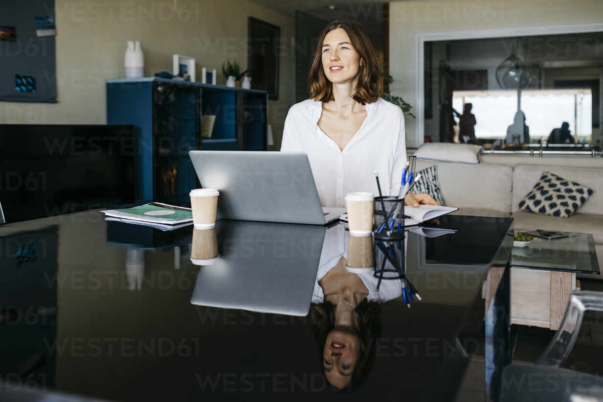 Woman working on table at home with notebook and laptop - JRFF03874 - Josep Rovirosa/Westend61