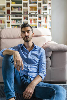 Portrait of serious young man sitting on the floor of living room at home - MGIF00817