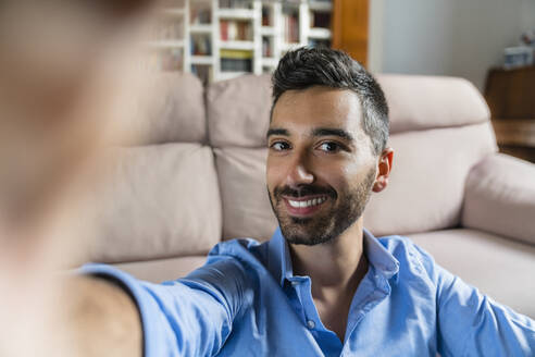 Portrait of smiling young man taking selfie at home - MGIF00820