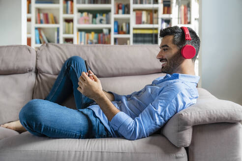 Smiling young man lying on the couch at home using smartphone and wireless headphones - MGIF00832