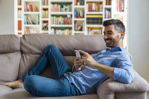 Smiling young man lying on the couch at home using smartphone - MGIF00835