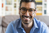 Portrait of happy young man wearing glasses  at home - MGIF00838