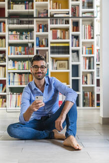 Portrait of smiling young man sitting with smartphone in front of bookshelves on the floor at home - MGIF00862