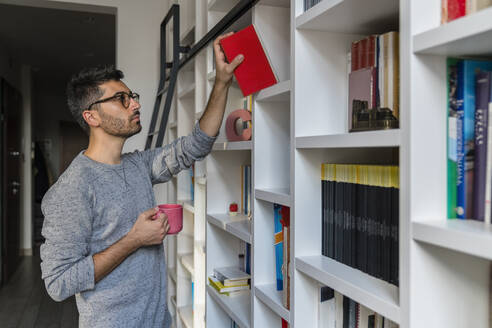 Portrait of young man with cup standing in front of bookshelves at home taking a book - MGIF00874