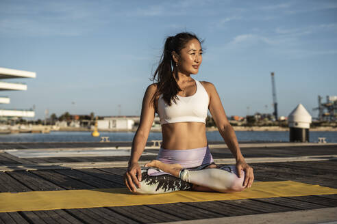 Asian woman practicing yoga on a pier at harbour - RCPF00095