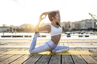 Asian woman practicing yoga on a pier at harbour at sunset, swan pose - RCPF00113