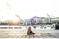 Asian woman practicing yoga on a pier at harbour at sunset, headstand with split - RCPF00116