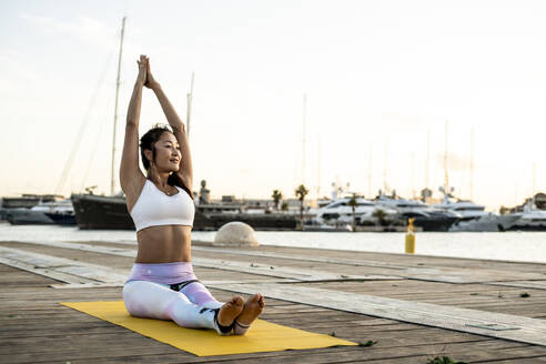 Asian woman practicing yoga on a pier at harbour - RCPF00119