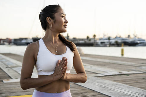 Asian woman practicing yoga on a pier at harbour in the evening light, prayer position - RCPF00122