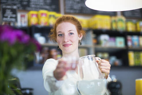 Young woman working in coffee shop, giving a water glass - SGF02433
