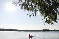 A boy with flamingo pool float on a lake - EYAF00654