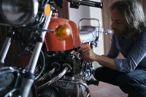 Young man checking his vintage motorbike parked in garage - JPIF00234