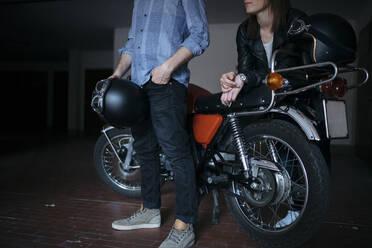 Couple with vintage motorbike parked in garage - JPIF00237