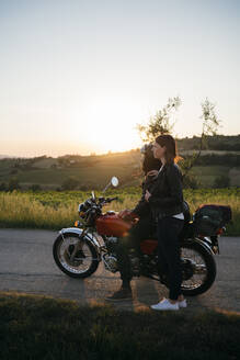 Young couple with vintage motorbike standing on country road at sunset looking at view, Tuscany, Italy - JPIF00240