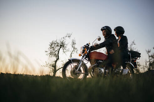 Young couple on vintage motorbike in rural scene at sunset - JPIF00246