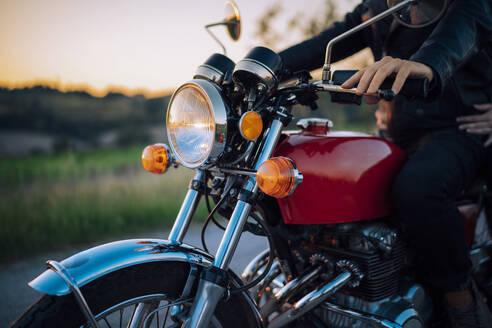 Crop shot of couple on vintage motorbike at sunset - JPIF00249