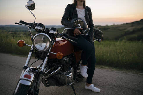 Crop shot of young woman with vintage motorbike on country road at sunset, Tuscany, Italy - JPIF00255