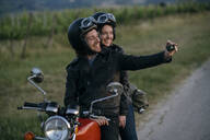 Portrait of happy young couple on vintage motorbike taking a selfie at roadside - JPIF00258