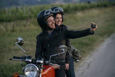 Portrait of happy young couple on vintage motorbike taking a selfie at roadside - JPIF00258