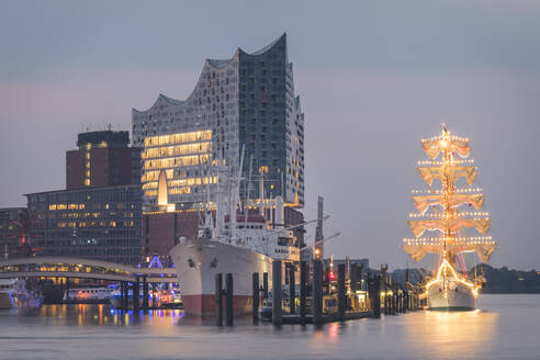 Germany, Hamburg, Mexican sailing training Cuauhtemoc moored on river near Elbphilharmonie at dusk - KEBF01413
