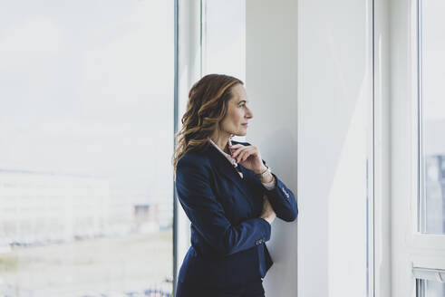 Mature businesswoman looking out of window in office - MOEF02521