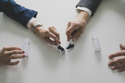 Close-up of businesswoman and businessman playing table football in office - MOEF02539