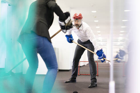 Businesswoman and businessman playing ice hockey in office - MOEF02545